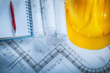 Building helmet checked notebook pen blueprints on construction
