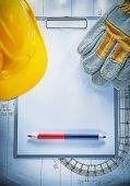 Clipboard pencil building helmet safety gloves on blueprint cons