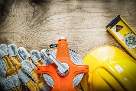 Construction level safety gloves measuring tape hard hat on wood