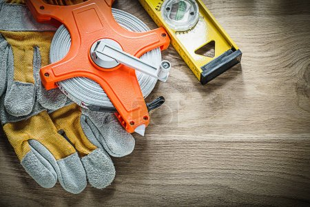 Construction level protective gloves tape measure on wooden boar