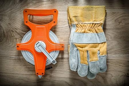 Pair of safety gloves measuring tape on wooden board
