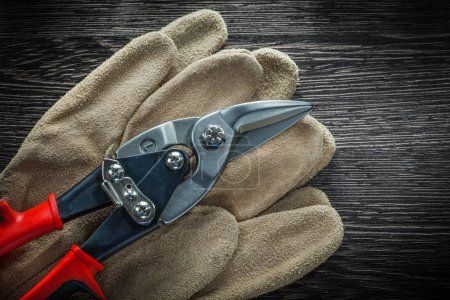 Protective gloves steel scissors on wooden board