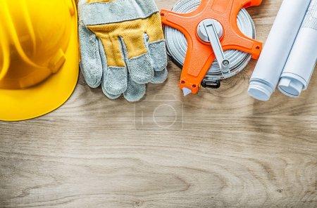 Rolled blueprints safety gloves tape measure hard hat on wooden