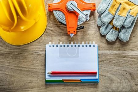 Notebook pencil safety gloves tape measure hard hat on wooden bo