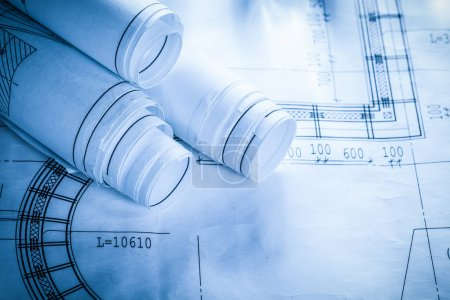 Rolled construction plans on blueprint