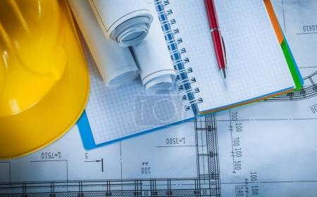 Safety hard hat checked notebook pen blueprints on construction