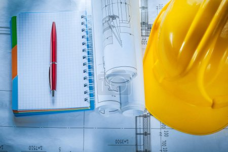 Safety building helmet checked notebook pen blueprints on constr
