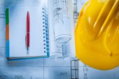 Safety building helmet checked notebook pen blueprints on constr