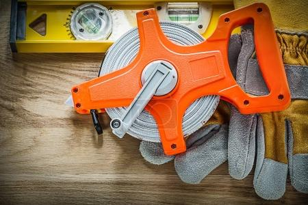 Construction level protective gloves measuring tape on wooden bo