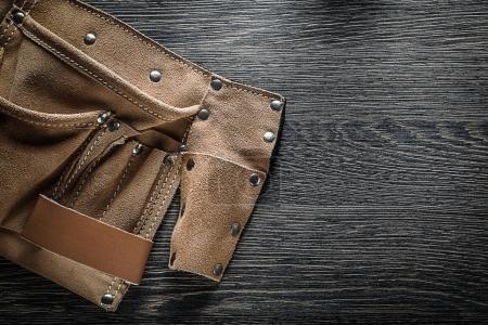 Leather tool belt on wooden board