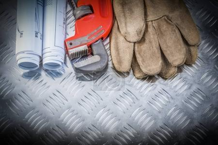 Photo for Pipe wrench construction plans leather safety gloves on corrugated metal background building concept. - Royalty Free Image