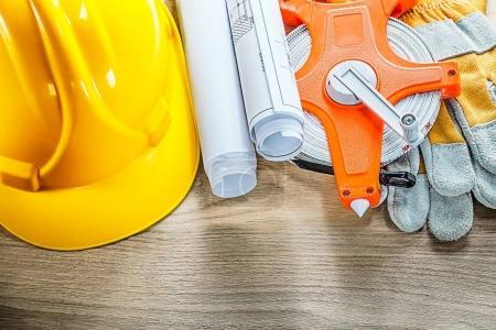 Rolled blueprints safety gloves tape measure building helmet on