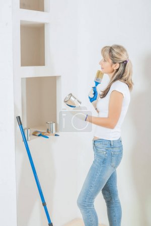 female painter with paint can and painbrush think