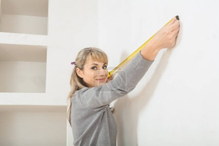 beautiful smiling female worker measuring wall with measure tape