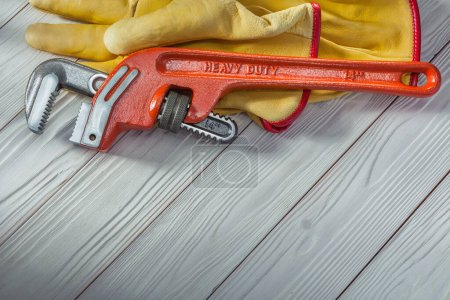 Photo for Construction tools red plumbers monkey wrench and yellow work gloves on white vintage wood - Royalty Free Image