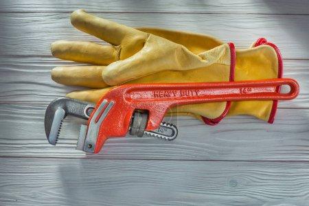 Foto de Llave de mono plomeros y guantes de trabajo de cuero amarillo en tableros de madera pintados blancos vintage - Imagen libre de derechos