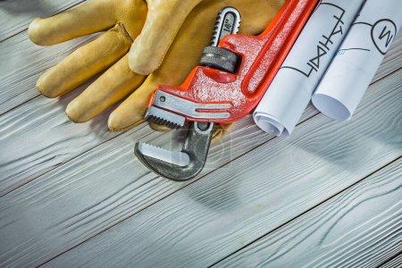 Photo pour Nouvelle clé à plomb gants en cuir et les plans de tuyauterie roulés sur fond de bois vintage - image libre de droit
