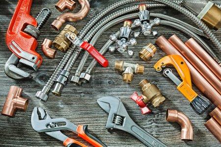 Photo pour Concept de plomberie grand ensemble d'accessoires de tuyauterie singe et clés réglables en plomb raccords en laiton cuivre coupe-tuyau sur fond de bois vintage - image libre de droit
