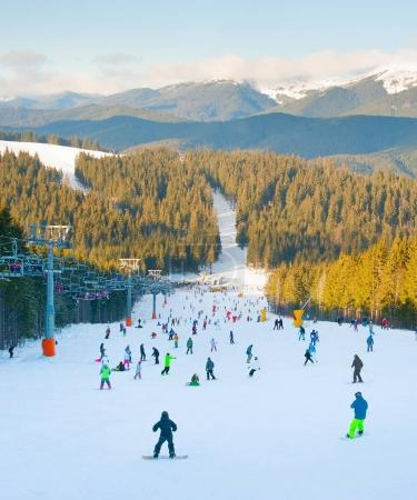 People skiing and snowboarding on slope