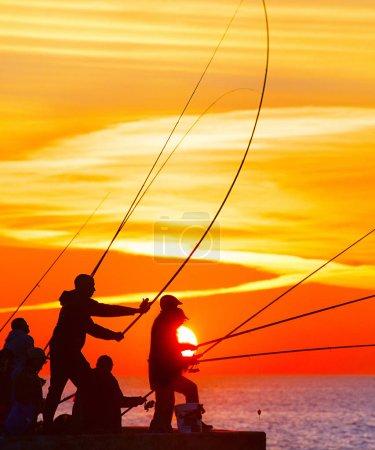 Fishermen fishing on pier