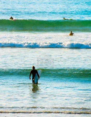 Surfers surf in ocean