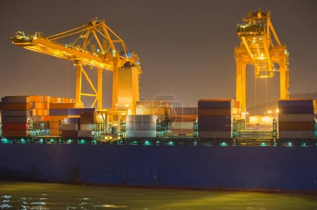 Cranes, ship and containers in a commercial port at night