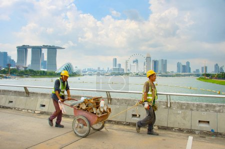 SINGAPORE - JAN 15, 2017: Two workers pushing a cart in front of Singapore Downtown. Construction industry is expected to pull in some $30 billion this year