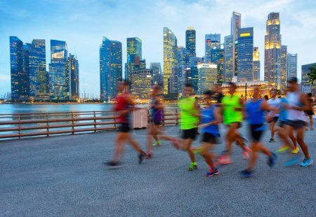 Group of runners on Singapore quayside at twilight, Singapore Downtown on a background