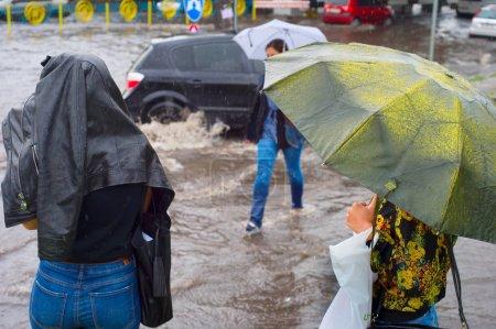 Women crossing flooded urban road in the heavy rain