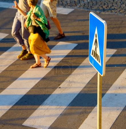 Crosswalk sign. People on background