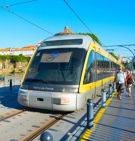 PORTO, PORTUGAL - JUNE 07, 2017: Train of Porto Metro on Dom Luis iron Bridge at sunset time. The network has 6 lines and reaches seven municipalities within the metropolitan Porto area.