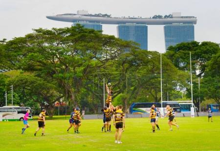 SINGAPORE - JANUARY 16TH, 2017: Two amateur rugby team play rugby in Singapore. Marina Bay Sands Hotel on background