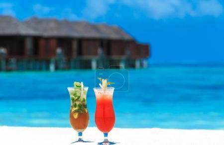 Photo pour Cocktails aux fruits dans des verres avec plage sur fond - image libre de droit