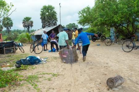 fishermen pull a fishing net in Sri Lanka