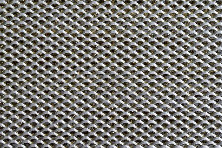 Background sheet of metal covered with lines of circular holes