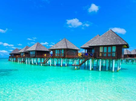 Row of bungalows in clean water and azure sky with clouds
