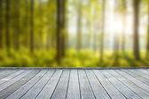 wooden deck table with forest background