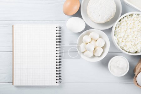 Dairy products on wooden table with notebook, top view