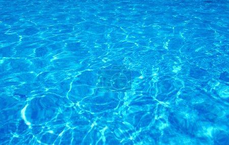 Photo pour Eau de piscine bleue avec reflets solaires - image libre de droit