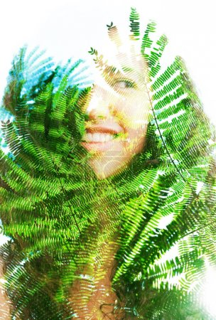 Double exposure portrait of beautiful woman with hair blending into texture of branches