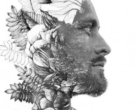 Photo pour Paintographie. Double exposition. Portrait en gros plan d'un homme aux traits forts et à la barbe légère se dissolvant derrière une aquarelle et une encre peintes à la main, en noir et blanc - image libre de droit