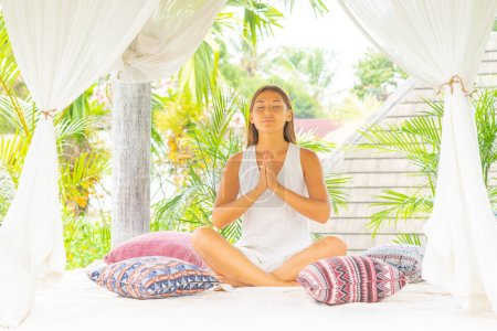 Young attractive woman meditating surrounded with tropical plants