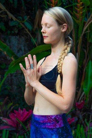Photo pour Une jolie dame qui pratique le yoga dans le jardin - image libre de droit