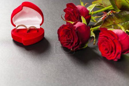 Photo for Beautiful red roses bouquet and wedding rings on black background - Royalty Free Image
