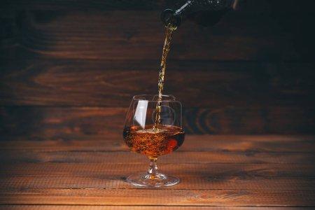 Photo pour Verser du brandy ou du cognac de la bouteille dans du verre sur un fond en bois - image libre de droit