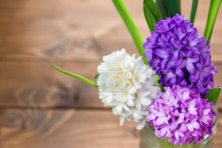 Foto de Fresh hyacinth flowers in vase on wooden background - Imagen libre de derechos