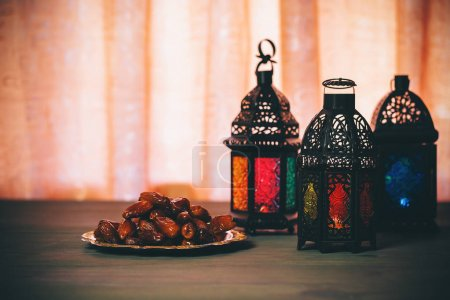 Photo for The Muslim feast of the holy month of Ramadan Kareem. Beautiful background with a shining lantern Fanus with dried dates. Free space for your text. - Royalty Free Image