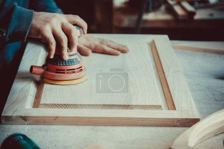 carpenter using sander for wood furniture