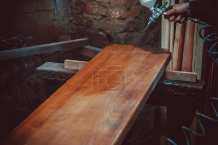Photo pour Maître peintre à l'usine, peinture industrielle de bois avec pistolet - image libre de droit