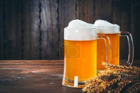 Photo for Two glasses of light beer with spikelets of barley on the wooden background. Beautiful background of the Oktoberfest - Royalty Free Image